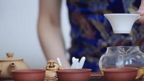 Το κορίτσι διοργανώνει skillfully μια τελετή τσαγιού, χύνει το ευώδες τσάι στα μικρά φλυτζάνια φιλμ μικρού μήκους