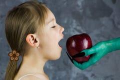 Το κορίτσι είναι έτοιμο να δοκιμάσει ένα μήλο από τη μάγισσα Το λευκό σαν το χιόνι παραμύθι Στοκ Φωτογραφία