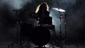 Το κορίτσι είναι λακτίσματα από τα τύμπανα παιχνιδιού, που παίζουν την ενεργητική μουσική Μαύρο υπόβαθρο καπνού σκιαγραφία κίνηση απόθεμα βίντεο