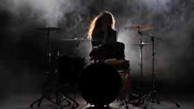 Το κορίτσι είναι λακτίσματα από τα τύμπανα παιχνιδιού, που παίζουν την ενεργητική μουσική Μαύρο υπόβαθρο καπνού σκιαγραφία απόθεμα βίντεο
