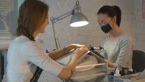 Το κορίτσι είναι αφαιρούμενες επιδερμίδες σε μια μηχανή μανικιούρ απόθεμα βίντεο