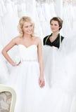 Το κορίτσι είναι ευτυχές να βάλει σε αυτό το γαμήλιο φόρεμα στοκ εικόνες