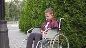 Το κορίτσι είναι με ειδικές ανάγκες άτομο σε μια αναπηρική καρέκλα απόθεμα βίντεο