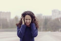 Το κορίτσι είναι στην οδό και φωνάζει κλείνοντας αυτιά με τα χέρια της Στοκ Εικόνες