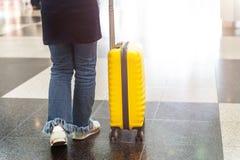 Το κορίτσι είναι στον αερολιμένα με τη φωτεινή και μοντέρνη βαλίτσα μεγέθους καμπινών ως έννοια διακοπών στοκ εικόνα
