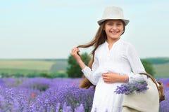 Το κορίτσι είναι στο lavender τομέα, όμορφο πορτρέτο, άσπρο φόρεμα, θερινό τοπίο Στοκ Εικόνα