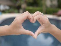 Το κορίτσι είναι χέρι-διαμορφωμένη καρδιά στοκ φωτογραφίες
