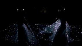 Το κορίτσι είναι χορεύοντας ένας δροσερός χορός πεταλούδων σε ένα φθορισμού κοστούμι με τις λάμπες φωτός απόθεμα βίντεο