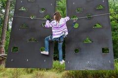 Το κορίτσι είναι 10 χρονών στην περιπέτεια αναρριμένος στο υψηλό πάρκο καλωδίων, πίσω άποψη, ενεργός τρόπος ζωής των παιδιών Στοκ Εικόνες
