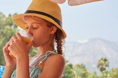 Το κορίτσι είναι drinkig φρέσκος χυμός, θερινό βουνό landsc Στοκ εικόνα με δικαίωμα ελεύθερης χρήσης