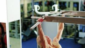 Το κορίτσι εκτελεί μια άσκηση ανύψωσης, ασκεί στον οριζόντιο φραγμό, αθλητική γυναίκα στη γυμναστική, που παίζει τον αθλητισμό ως φιλμ μικρού μήκους