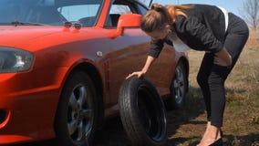 Το κορίτσι δεν ξέρει πώς να αλλάξει μια ρόδα αυτοκινήτων απόθεμα βίντεο