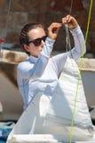 Το κορίτσι εξασφαλίζει ένα πανί πρίν βγαίνει στη θάλασσα Στοκ Εικόνες