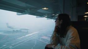 Το κορίτσι εξετάζει το αεροπλάνο από το τερματικό αερολιμένων απόθεμα βίντεο