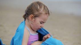 Το κορίτσι εξετάζει το θαλασσινό κοχύλι απόθεμα βίντεο
