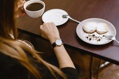 Το κορίτσι εξετάζει το ρολόι σε έναν καφέ πέρα από ένα φλιτζάνι του καφέ χρόνος στο ρολόι - ο χρόνος για το πρόγευμα, επιδόρπιο στοκ εικόνα