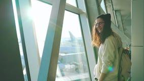 Το κορίτσι εξετάζει το ρολόι στο τερματικό αερολιμένων απόθεμα βίντεο