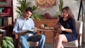 Ο τύπος και το κορίτσι κάθονται στην εγχώρια βιβλιοθήκη Το κορίτσι εξετάζει το τηλέφωνο, ο τύπος διαβάζει ένα βιβλίο απόθεμα βίντεο