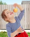 Το κορίτσι εξετάζει το μήλο Στοκ Φωτογραφίες