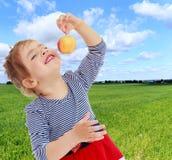 Το κορίτσι εξετάζει το μήλο Στοκ Εικόνες