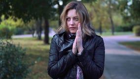Το κορίτσι επάγωσε στο πάρκο φθινοπώρου η νέα γυναίκα τύλιξε σε ένα μαντίλι και αναπνέει σε ετοιμότητα του για να τους θερμάνει ε φιλμ μικρού μήκους