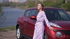 Το κορίτσι επιθεωρεί ένα νέο αυτοκίνητο, κλίνει στην κουκούλα και εξετάζει τη φύση r απόθεμα βίντεο