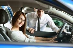 Το κορίτσι επιλέγει το νέο αυτοκίνητο στοκ φωτογραφία