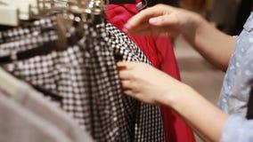 Το κορίτσι επιλέγει τα ενδύματα στο κατάστημα απόθεμα βίντεο