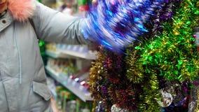 Το κορίτσι επιλέγει τις διακοσμήσεις διακοπών Χριστουγέννων στη λεωφόρο απόθεμα βίντεο