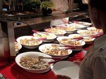 Το κορίτσι επιλέγει ότι τα τρόφιμα σε μια ασιατική αμοιβή-τι-εσύ-ανάγκη εστιατορίων επιλέγουν μεταξύ των πολυάριθμων egozotic πιά στοκ εικόνα με δικαίωμα ελεύθερης χρήσης