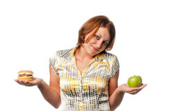 Το κορίτσι επιλέγεται μεταξύ του μήλου και του χάμπουργκερ στοκ φωτογραφία με δικαίωμα ελεύθερης χρήσης