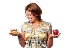 Το κορίτσι επιλέγεται μεταξύ του μήλου και του χάμπουργκερ στοκ εικόνα με δικαίωμα ελεύθερης χρήσης