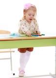 Το κορίτσι επισύρει την προσοχή σε ένα φύλλο του εγγράφου Στοκ Εικόνες