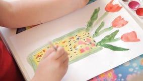 Το κορίτσι επισύρει την προσοχή στα λουλούδια εγγράφου σε ένα βάζο, μια βούρτσα με το χρώμα watercolor φιλμ μικρού μήκους