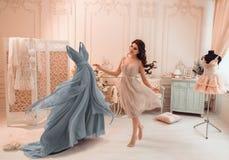 Το κορίτσι επιλέγει ένα φόρεμα στοκ φωτογραφίες