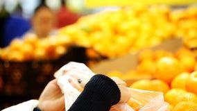 Το κορίτσι επιλέγει τα πορτοκάλια σε μια υπεραγορά φιλμ μικρού μήκους