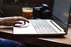 Το κορίτσι εργάζεται στον υπολογιστή Τα θηλυκά χέρια λειτουργούν στον υπολογιστή, τη κάμερα και τον καφέ στο υπόβαθρο Στοκ εικόνες με δικαίωμα ελεύθερης χρήσης