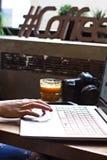 Το κορίτσι εργάζεται στον υπολογιστή Τα θηλυκά χέρια λειτουργούν στον υπολογιστή, τη κάμερα και τον καφέ στο υπόβαθρο Στοκ Εικόνα