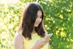 το κορίτσι 14 ετών διαβάζει sms στο τηλέφωνο Στοκ Φωτογραφίες