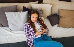 Το κορίτσι εφήβων έχει τη διασκέδαση με την κινητή τοποθέτηση στο κρεβάτι ακούοντας τη μουσική από ένα smartphone Στοκ Εικόνες