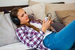 Το κορίτσι εφήβων έχει τη διασκέδαση με την κινητή τοποθέτηση στο κρεβάτι ακούοντας τη μουσική από ένα smartphone Στοκ εικόνες με δικαίωμα ελεύθερης χρήσης