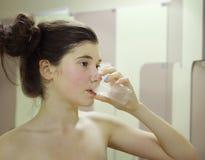 Το κορίτσι εφήβων αθλητικών τύπων πίνει το νερό από το πλαστικό ποτήρι Στοκ Εικόνες