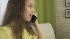 Το κορίτσι εφήβων αποσπάται από τη τηλεφωνική συζήτηση κάνοντας την εργασία της Στοκ φωτογραφία με δικαίωμα ελεύθερης χρήσης