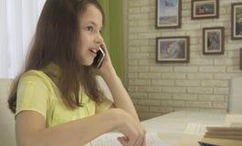 Το κορίτσι εφήβων αποσπάται από τη τηλεφωνική συζήτηση κάνοντας την εργασία της Στοκ εικόνα με δικαίωμα ελεύθερης χρήσης