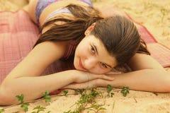 Το κορίτσι εφήβων βάζει στη στενή επάνω φωτογραφία παραλιών στοκ εικόνα