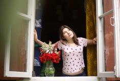 Το κορίτσι εφήβων εξετάζει από το παράθυρο το πρωί φ Στοκ Εικόνα