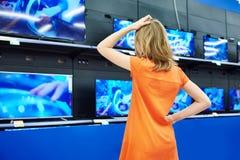 Το κορίτσι εφήβων εξετάζει τις TV LCD στο κατάστημα Στοκ Φωτογραφίες