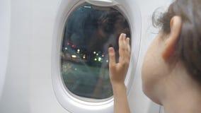 Το κορίτσι εφήβων λέει αντίο να κυματίσει τον τρόπο ζωής χεριών του στο παράθυρο της έννοιας αεροσκαφών αεροπορίας αεροπλάνων το  απόθεμα βίντεο