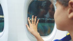 Το κορίτσι εφήβων λέει αντίο να κυματίσει το χέρι του στο παράθυρο του τρόπου ζωής έννοιας αεροσκαφών αεροπορίας αεροπλάνων το νέ απόθεμα βίντεο
