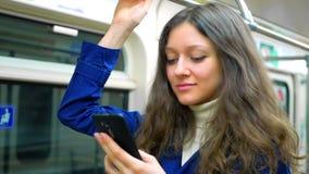 Το κορίτσι εφήβων οδηγά τον υπόγειο και το χρησιμοποιημένο smartphone φιλμ μικρού μήκους